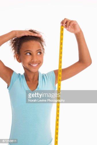 Girl measuring height : Stock Photo