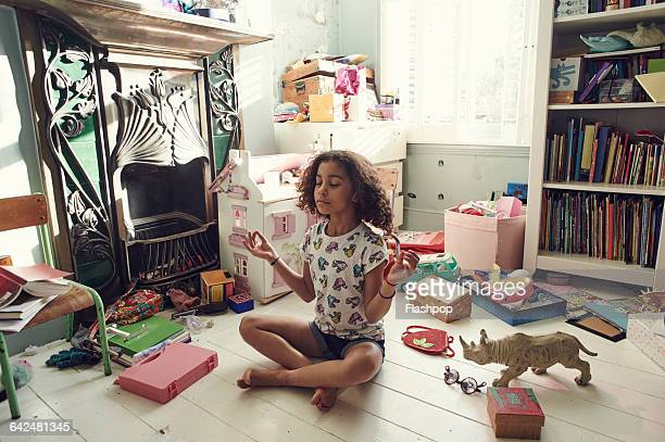 Girl meditating in bedroom