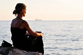 Woman contemplating on the beach at sunrise.