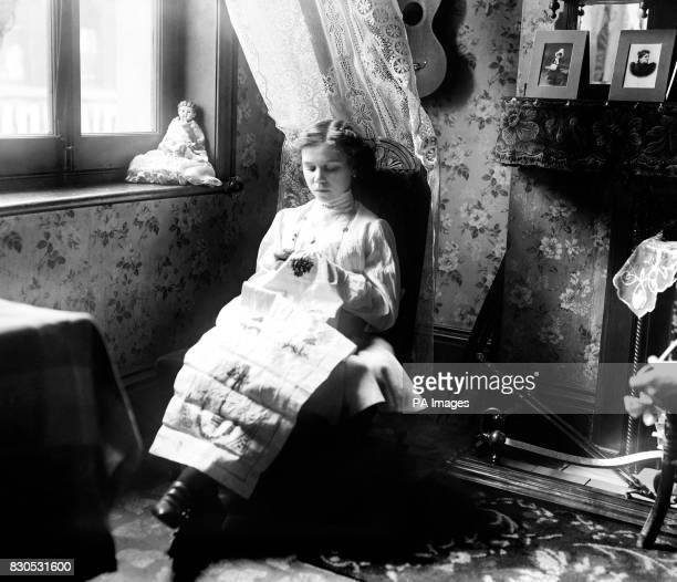 A girl member of the 'Butterflies' sits by the window to take advantage of the bright sunshine for her sewing
