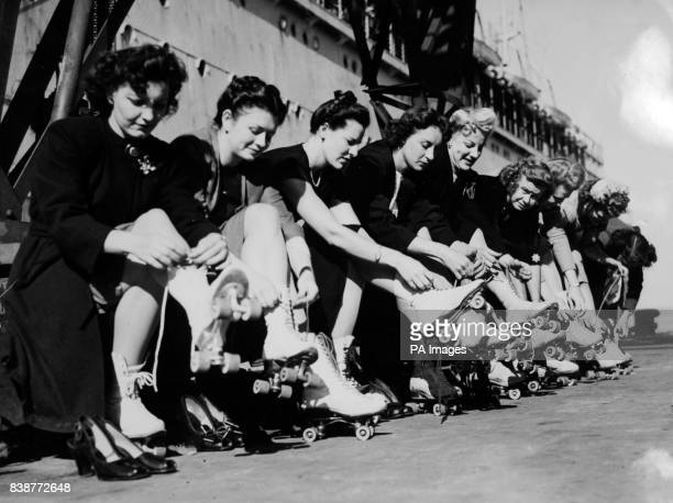 Girl members of the roller speedway teams put on their skates to find their landlegs again on the quayside at Southampton Left to right Dorothy Rocco...