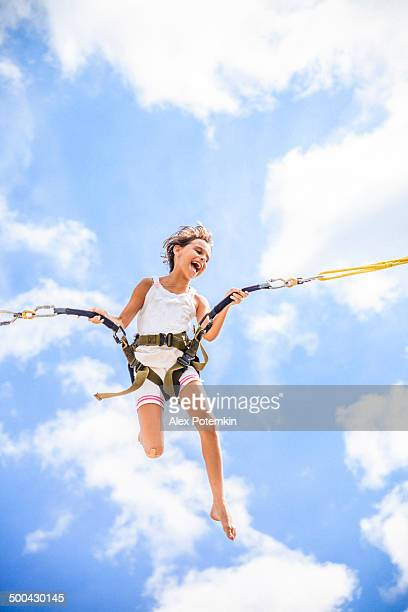 Girl mid air from bungee jumping