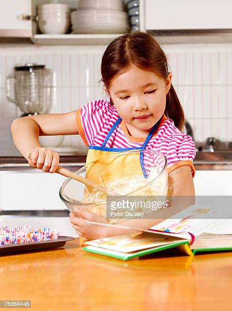 Girl (6-7) mixing dough in bowl, looking at cookery book