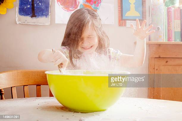 girl (4-5) mixing flour in bowl