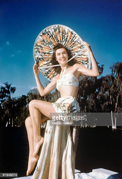 Girl modeling a swim suit and huge sunbonnet