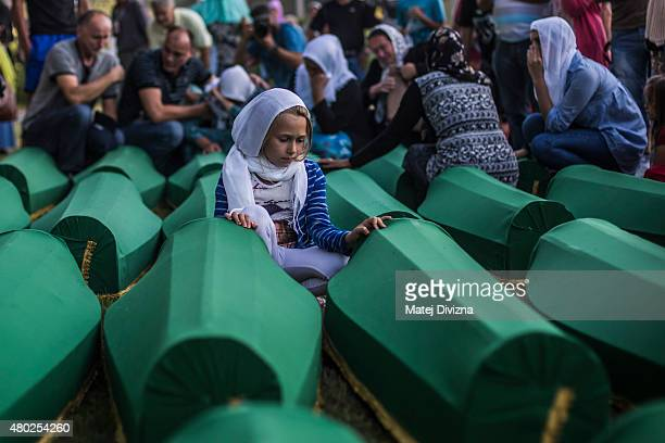 A girl mourns over a coffin among 136 coffins of victims of the 1995 Srebrenica massacre at the Potocari cemetery and memorial near Srebrenica on...