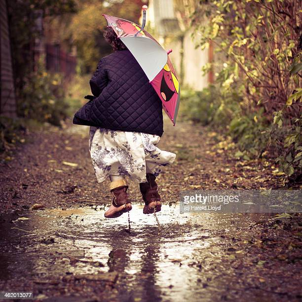 Girl muddy puddle jumping with smiling umbrella