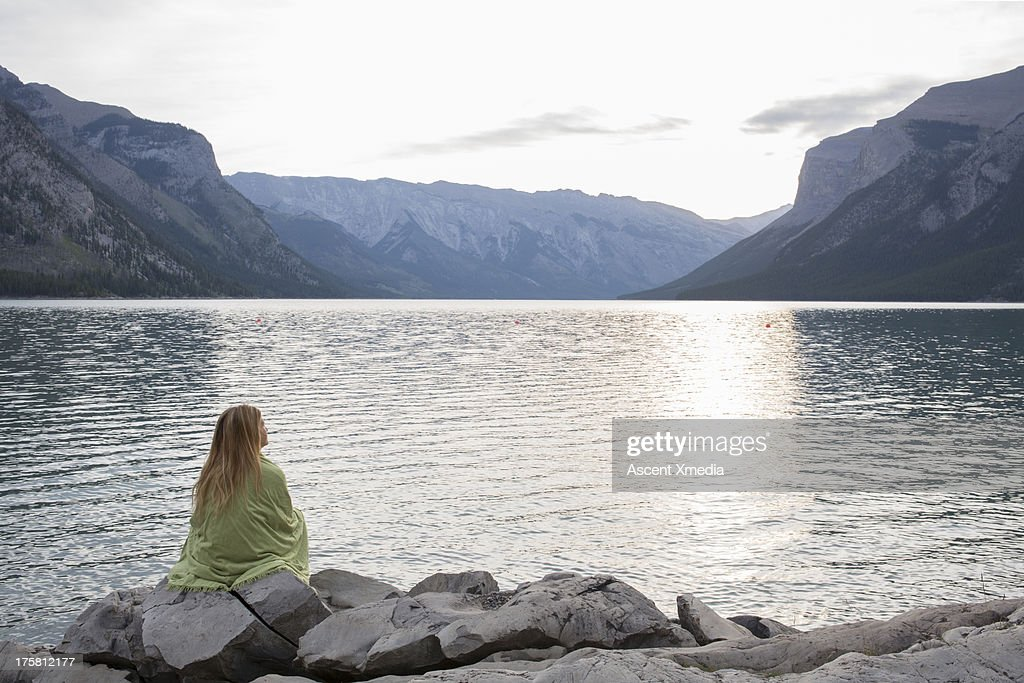 Girl nestles under blanket at lake edge, mtns