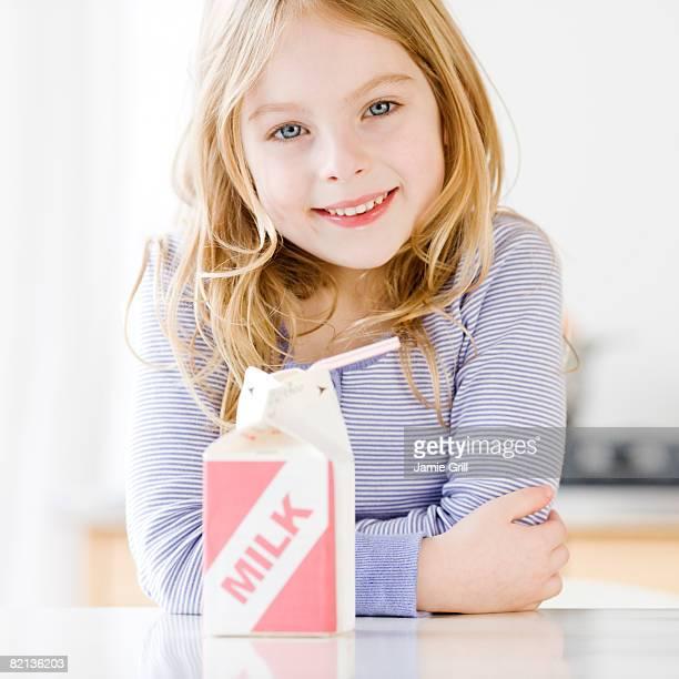 Girl next to carton of milk