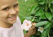 Girl next to mandevilla plant