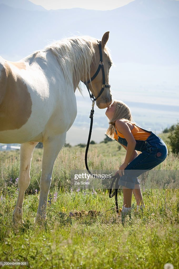 Girl (9-11) nuzzling horse, side view : Stock Photo