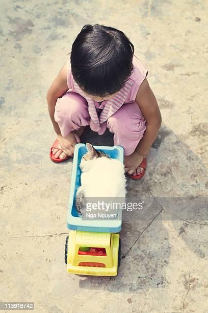 Girl observing kitten sleeping in toy truck