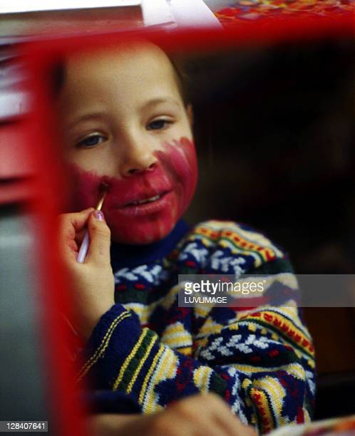 girl of 6 busy with red clown face paint