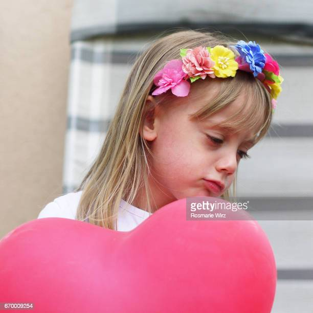 Girl of five holding pink balloon, sulky expression