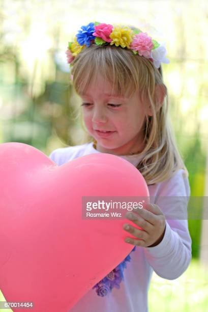 Girl of five holding pink heart-shaped balloon, smiling