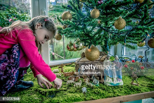 Girl of Four Playing with Figurines at Nativity Scene, Europe