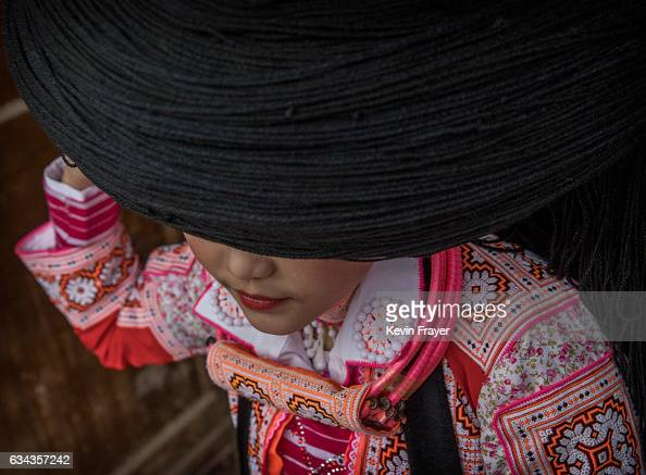 A girl of the Long Horn Miao ethnic minority group has her headdress put on her before Tiaohua or Flower Festival as part of the Lunar New Year on...