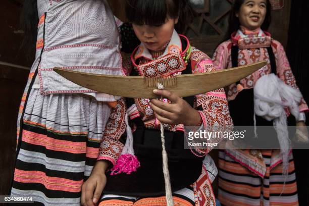 A girl of the Long Horn Miao ethnic minority group holds a wooden hairclip as she has her headdress put on her before Tiaohua or Flower Festival as...