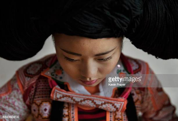 A girl of the Long Horn Miao ethnic minority group waits as a headdress is put on her before Tiaohua or Flower Festival as part of the Lunar New Year...
