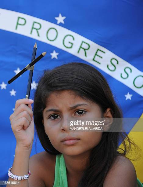 A girl of the Tasso da Silveira municipal school in Rio de Janeiro which had suffered an attack on April 2011 that left 12 dead and 10 injured holds...