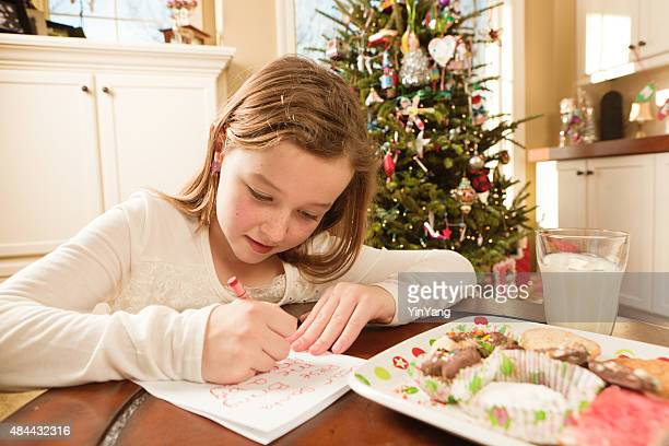 Girl Offering Cookies and Christmas Wish List to Santa
