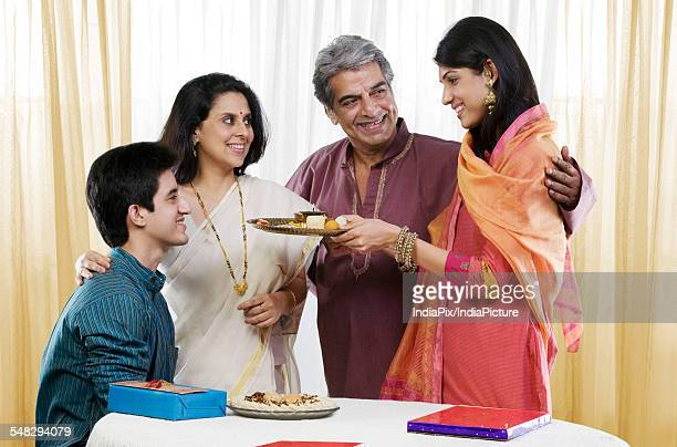 Girl offering sweets during Rakhi