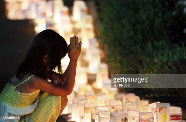 A girl offers a prayer for Abomb victims before lanterns placed at the Peace Memorial Park in Nagasaki Japan's southern island of Kyushu on August 8...