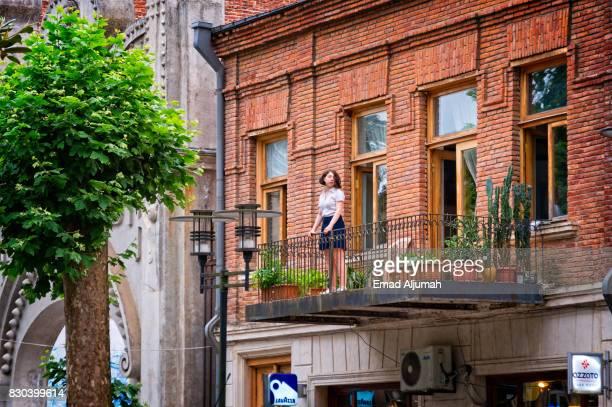 Girl on a balcony in downtown Kutaisi, Georgia - June 27, 2017