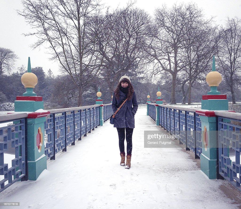 A girl on a bridge in a snowy day