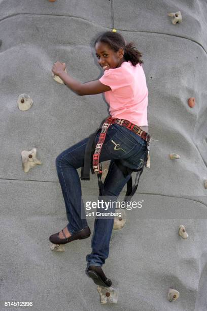 A girl on a rock climbing wall at the Easter Eggstravaganza at Margaret Pace Park