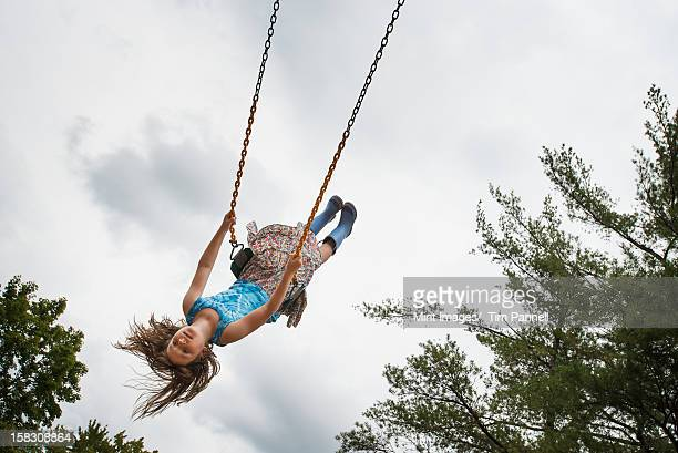 A girl on a rope swing high in the air