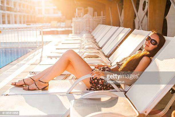 Girl on a sun lounger by the pool