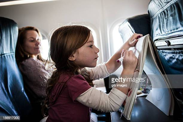 Girl (6yrs) on airplane, drawing on tablet