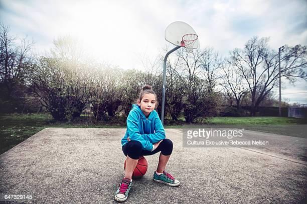 Girl on basketball court sitting on basketball