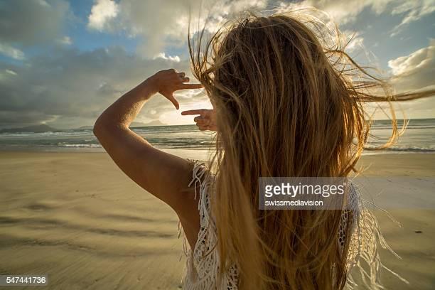 Girl on beach frames sunset into fingers