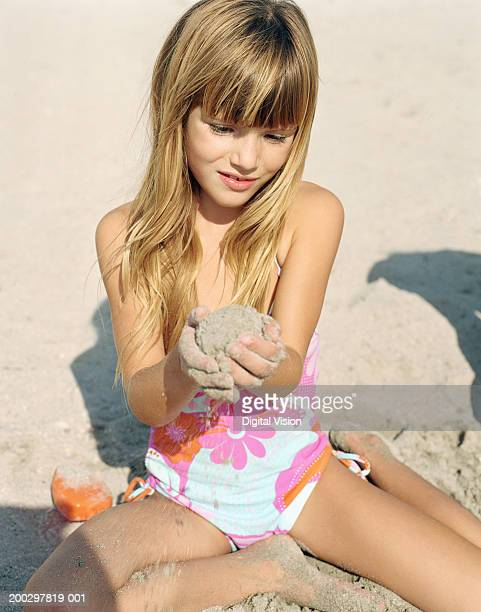 Girl (6-8) on beach, holding ball of wet sand, smiling, close-up