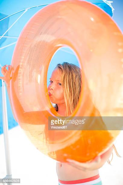 Girl on beach inflating an orange floating tyre