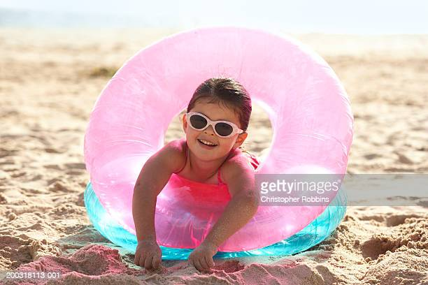 Girl (2-4) on beach, leaning through inflatable rings, portrait