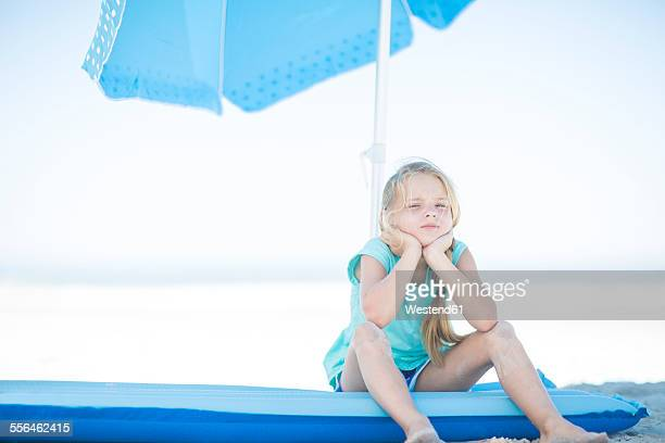 Girl on beach sitting on a lilo