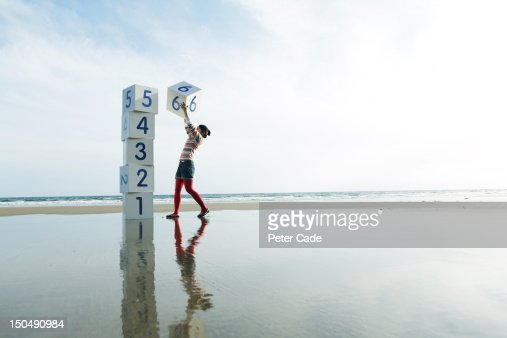 Girl on beach stacking numbered boxes : Stock Photo