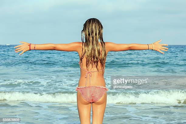 Girl on beach with outstretched arms