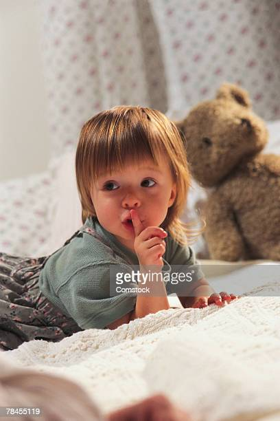 Girl on bed gesturing for quiet