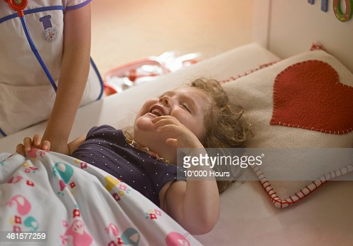 3 YO girl on bed laughing playing doctors : Stock Photo