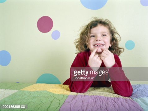 Girl (4-6) on bed pointing at missing teeth, smiling : Stock Photo
