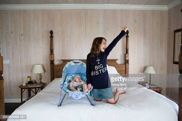 Girl (6-8) on bed with baby brother (3-6 months), cheering