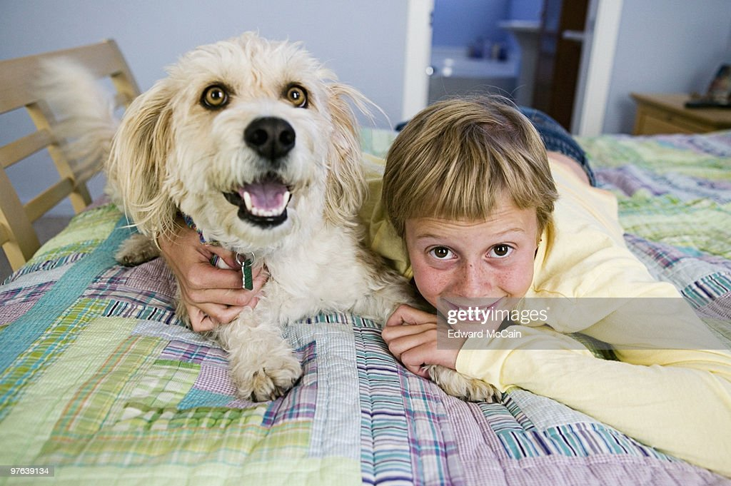 Girl on bed with dog : Stock Photo