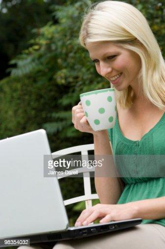 girl on computer with mug : Stock Photo