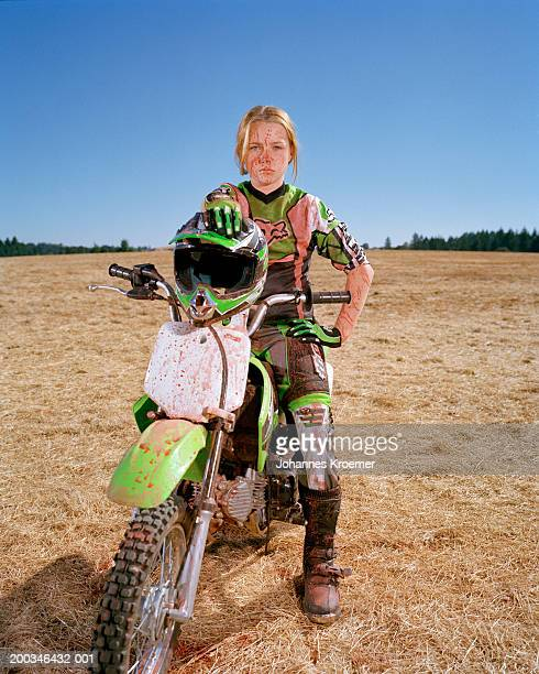 Girl (11-13) on dirt bike splattered with paint, portrait