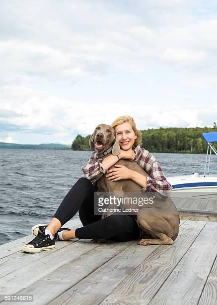 girl on dock hugging weimaraner dog