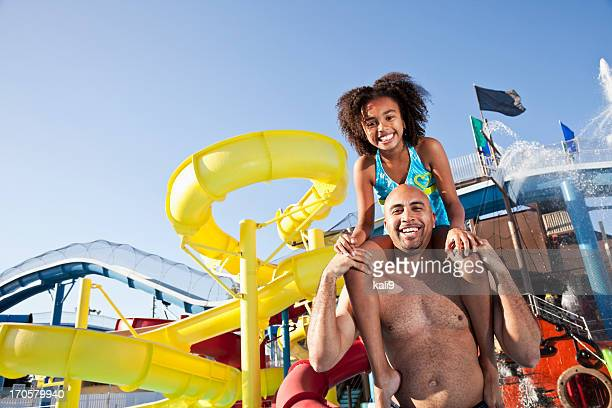 Girl on father's shoulders at water park